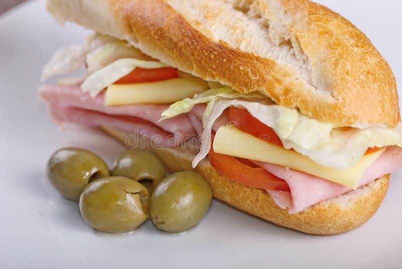 Sandwich fait maison avec du jambon, la salade, le chesse et les tomates en baguette de pain blanc photo stock