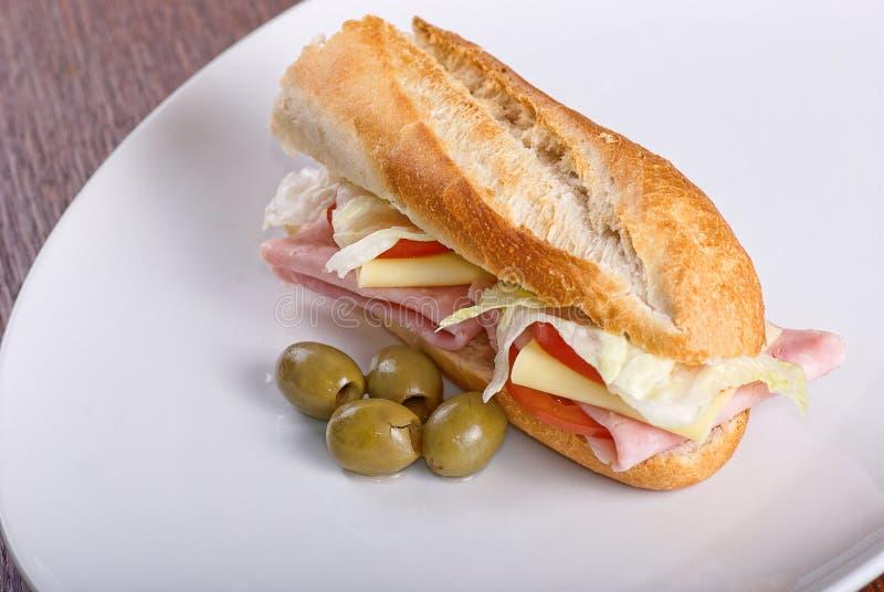 Sandwich fait maison avec du jambon, la salade, le chesse et les tomates en baguette de pain blanc photos libres de droits
