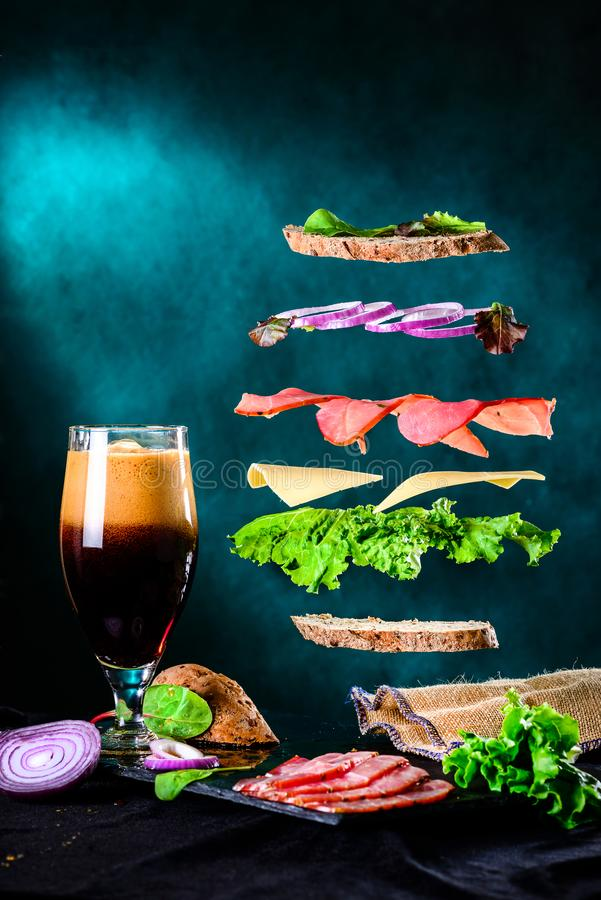 Sandwich with falling ingredients in the air and dark beer in a royalty free stock photo