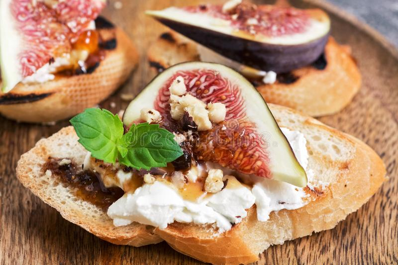 A sandwich with figs, cheese, nuts and honey. Selective focus, close-up. stock photo