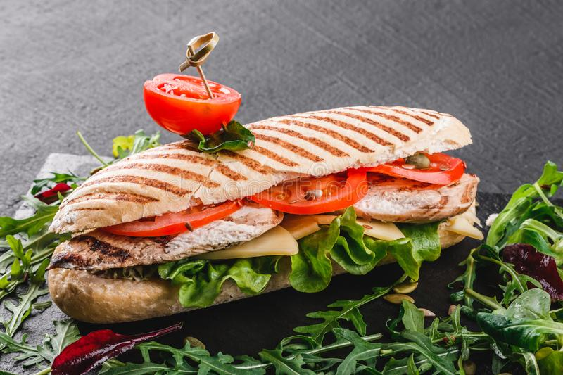 Sandwich with fillet grilled chicken, fresh vegetables, cheese and greens on black shale board over black stone background. Healthy food concept. Top view stock photos
