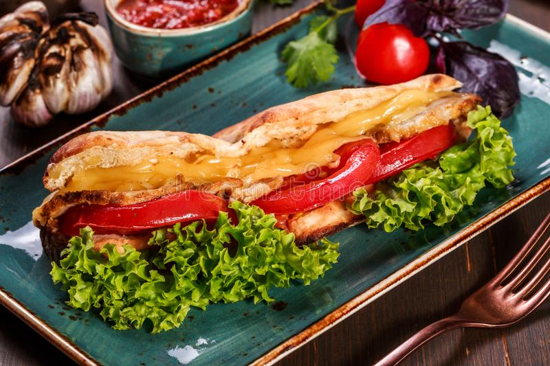 Sandwich with fillet grilled chicken, lettuce, tomatoes, cheese and traditional bread loaf. Out of the oven on dark background. Sandwich ingredients. Delicious stock image