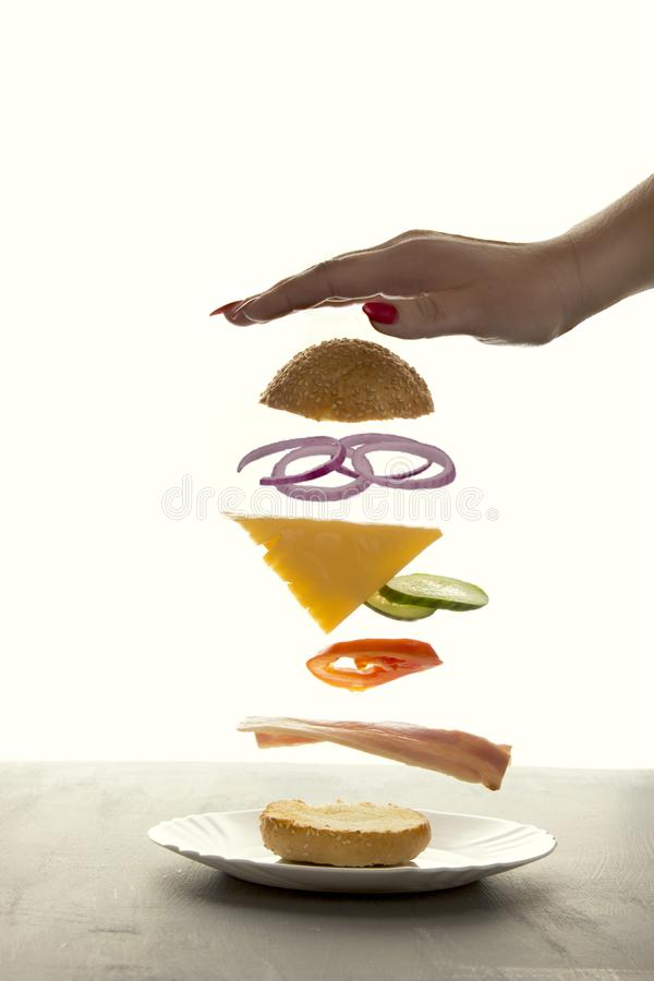 Sandwich floating in the air on a white background. The sandwich rises behind the woman`s hand, the power of levitation stock photography