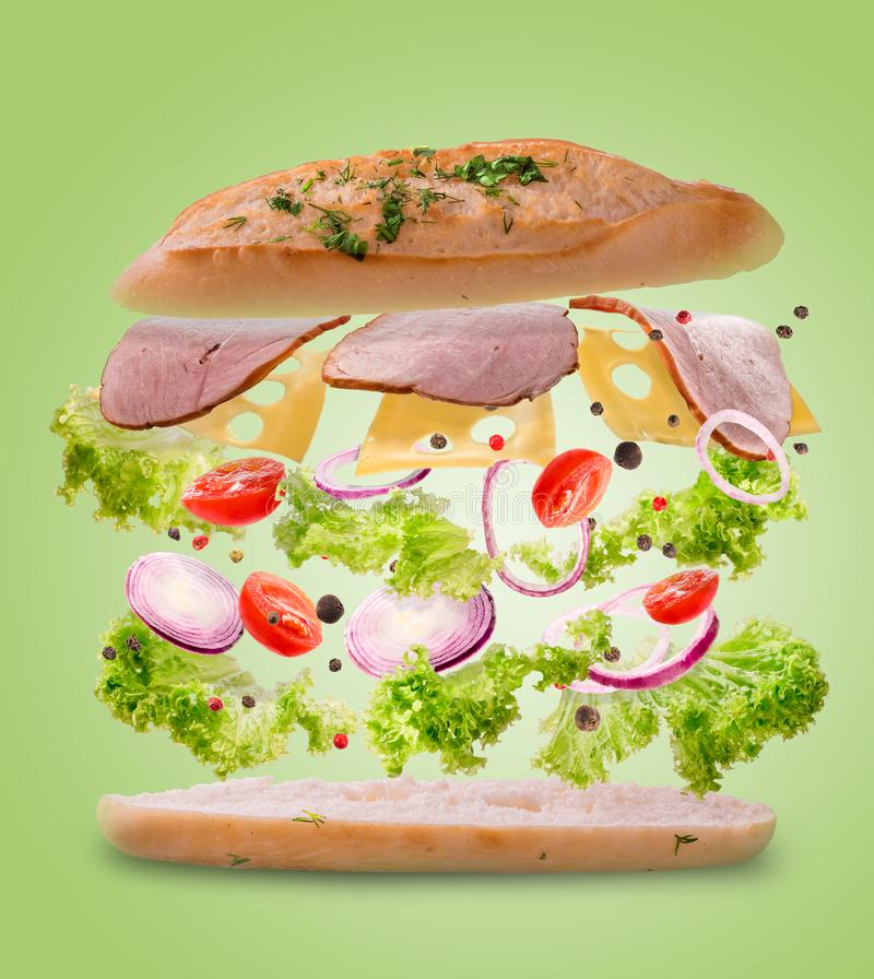 Sandwich with flying ingredients. Freeze motion. Close-up. lime green background. royalty free stock image