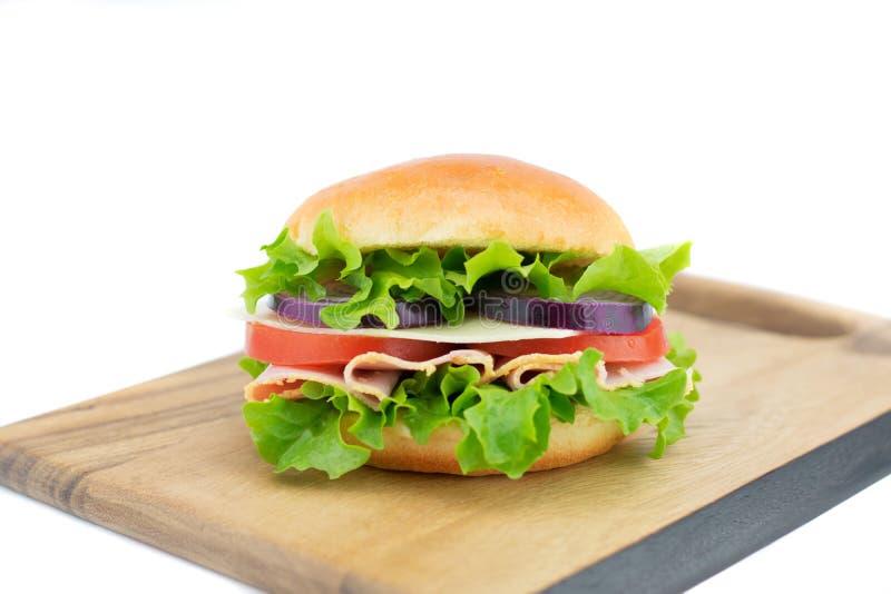 Sandwich frais avec les légumes et le jambon sur le conseil en bois images libres de droits