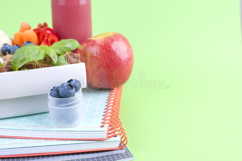 Sandwich and fresh juice with fruit in a lunch box on a bright background. A healthy lunch for the shawls, office and university. royalty free stock photo