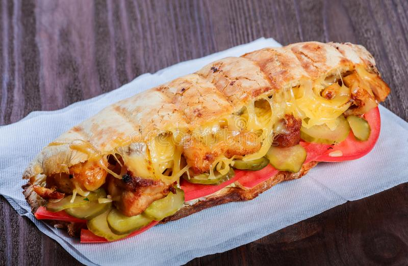 Sandwich from fresh pita bread with fillet grilled chicken, lettuce, slices of fresh tomatoes, pickles and cheese. On dark wooden background. Shashlik or Shish royalty free stock images