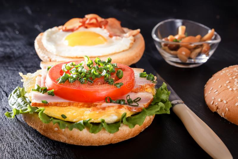 Sandwich with fried egg, bacon, tomato, greens. Breakfast with fried potatoes and mushrooms royalty free stock image