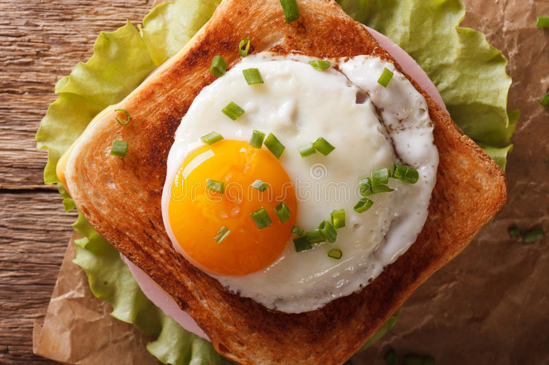 Sandwich with fried egg, ham, onions and cheese close up. horizontal top view stock photography