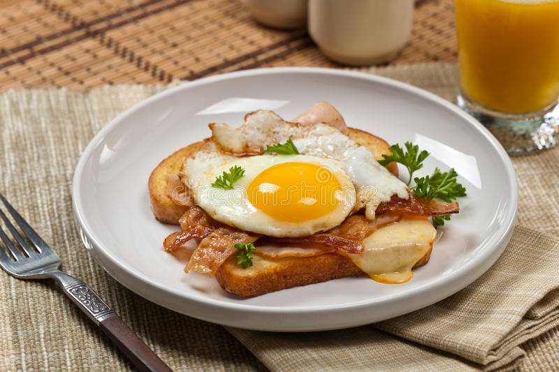 Sandwich with fried eggs. Traditional French Toasted Sandwich with fried eggs - Croque Madame. Selective focus stock photo