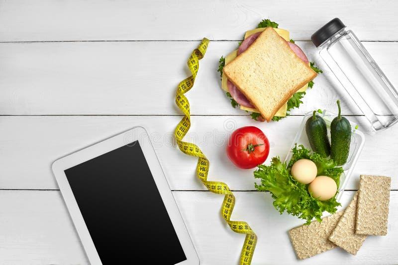 Sandwich, Frischgemüse, Flasche Wasser und Eier auf einer Tabelle mit einer Tablette, Draufsicht Kopieren Sie Platz lizenzfreies stockbild