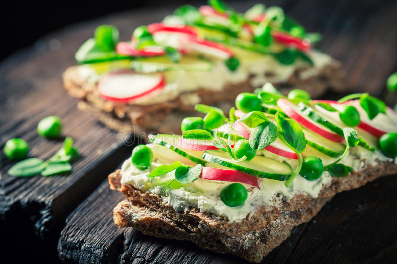 Sandwich with fromage cheese, avocado and bread. On old wooden table stock image