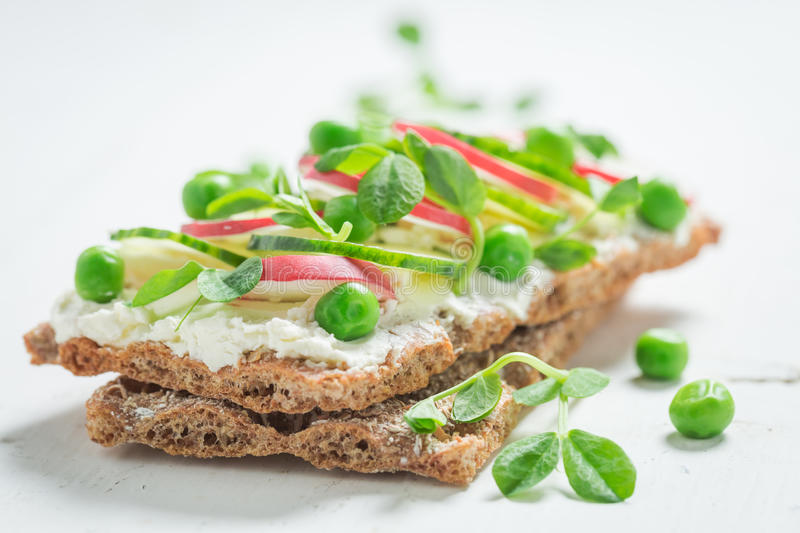 Sandwich with fromage cheese, avocado and crunchy bread. On old white table stock photo
