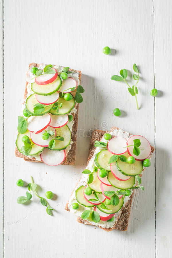 Sandwich with fromage cheese, avocado and radish. On old white table stock photography