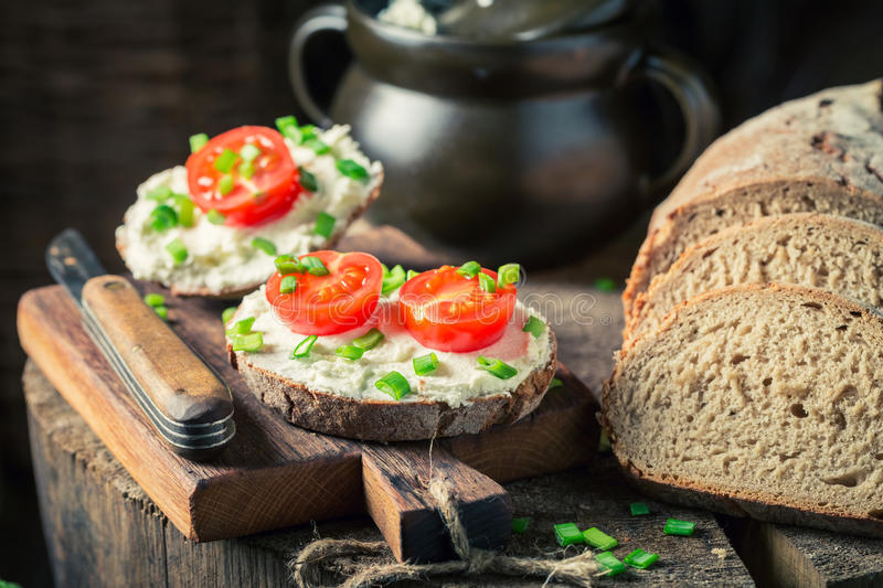 Sandwich with fromage cheese, chive and cherry tomatoes. On old wooden table royalty free stock photography