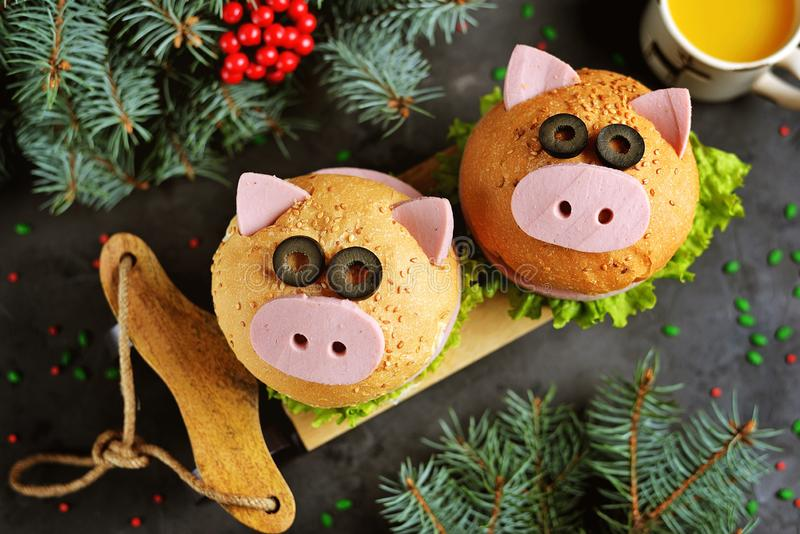 Sandwich with ham, cheese and lettuce in the form of cute pig - symbol of 2019. Children`s breakfast. Christmas background. Top vi stock image