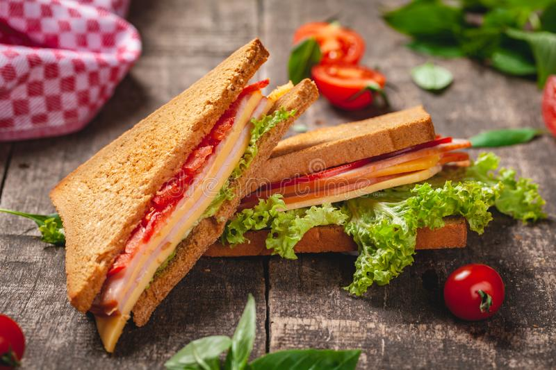 Sandwich with ham, cheese, tomatoes and lettuce leaves on wooden rustic table royalty free stock image
