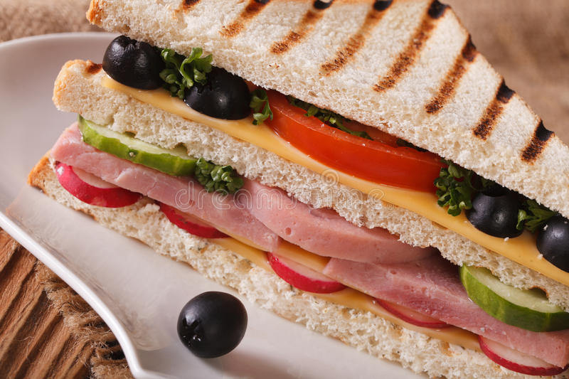 Sandwich with ham, cheese and vegetables macro on a plate royalty free stock image