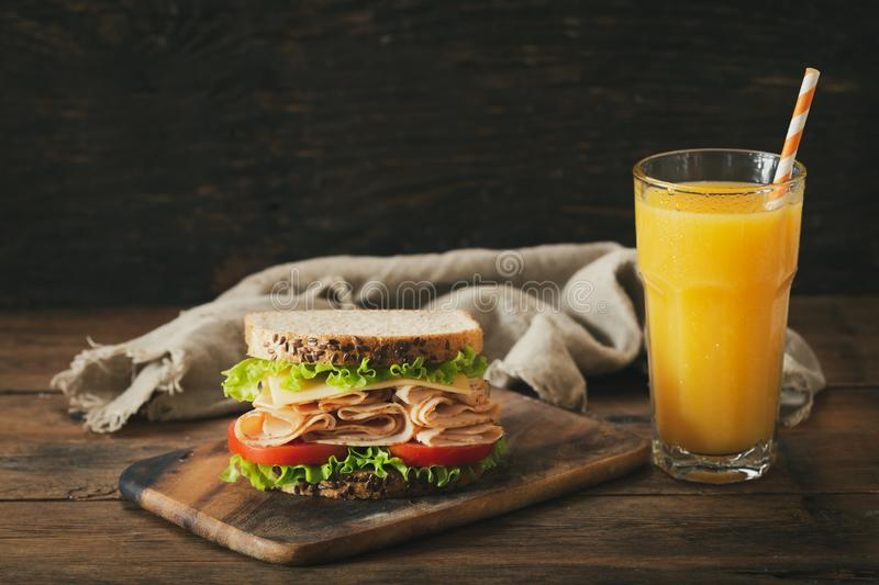 Sandwich with ham and glass of orange juice stock photography