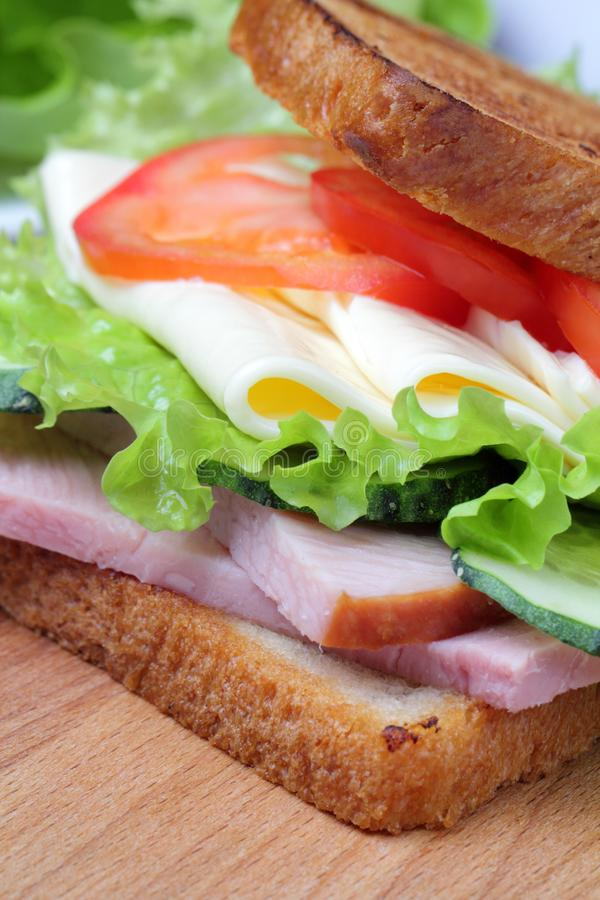 Ham, lettuce, slices of cheese, tomatoes, on a cutting board stock photography