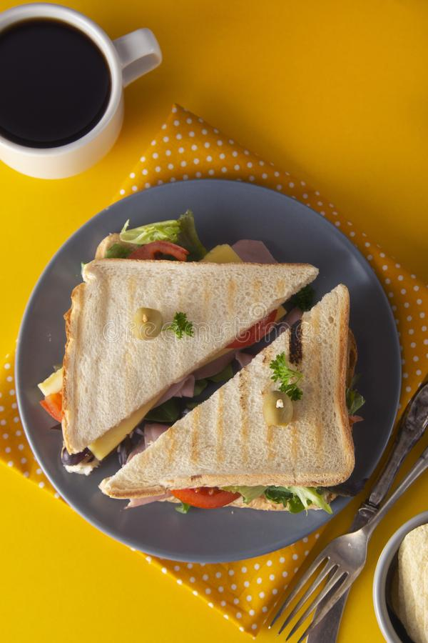 Sandwich with ham. Toasted double panini with ham, cheese fresh vegetables.Yellow background. Copy space food lettuce turkey olive bread meat lunch snack meal stock photo