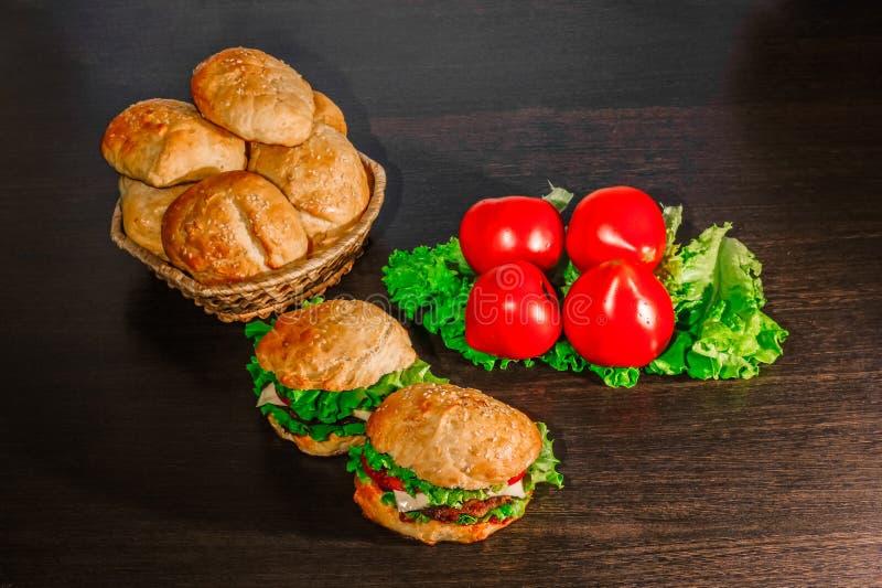 Sandwich - hamburger avec l'hamburger, le fromage, la tomate, et l'oignon sur le fond en bois photographie stock