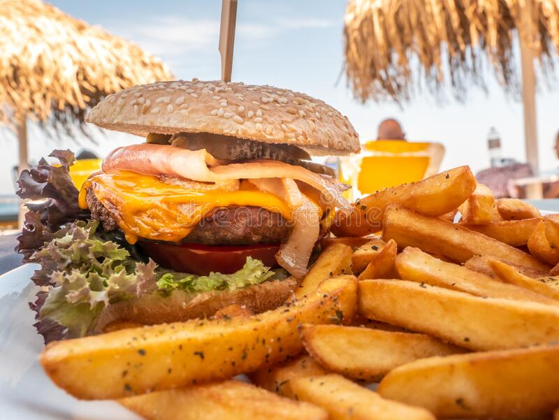 Sandwich with hamburger for lunch on beach royalty free stock photo