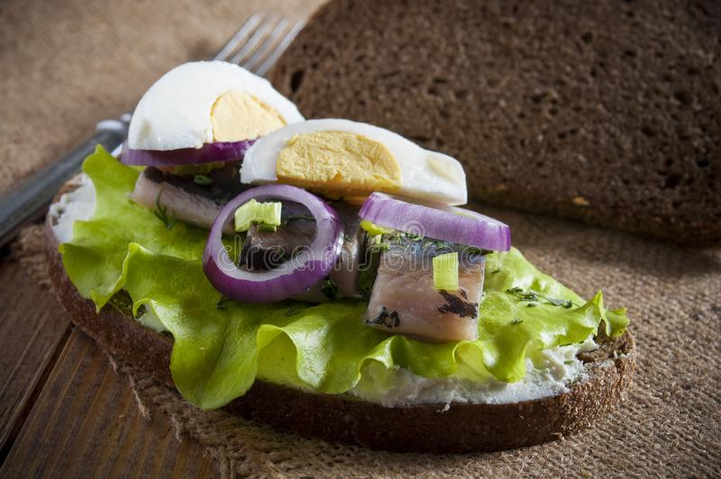 Sandwich with herring fillet, lettuce, dill , chives, onion, cream and eggs. Near dark rye bread and fork on burlap. Close-up royalty free stock images