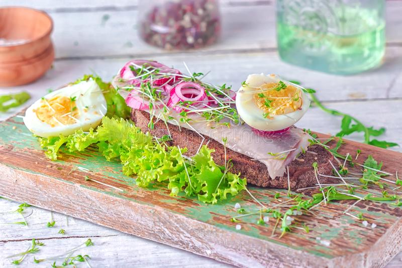 Sandwich with herring fillets with fresh green salad, onion ring, a half of eggs and micro greens on the wooden desk royalty free stock image