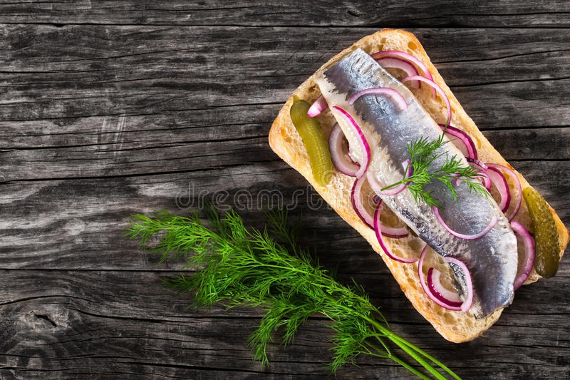 Sandwich with herring fillets, onion, pickled cucumber and dill royalty free stock image