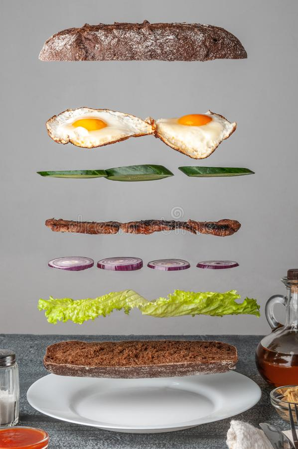 Sandwich ingredients are levitated in the air with crispy baguette, lettuce, cucumber, red onion, grill meat and scrambled eggs. royalty free stock photos