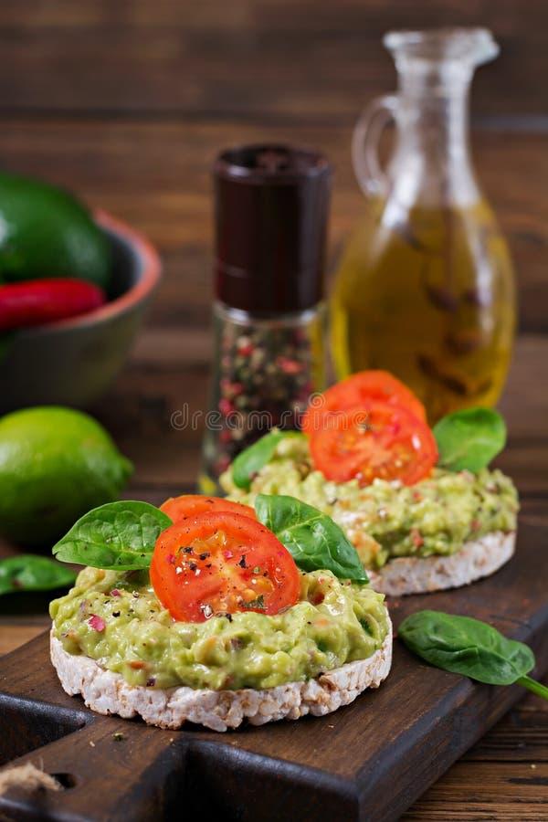 Sandwich kernachtig brood met guacamole en tomaten op een houten achtergrond stock foto's
