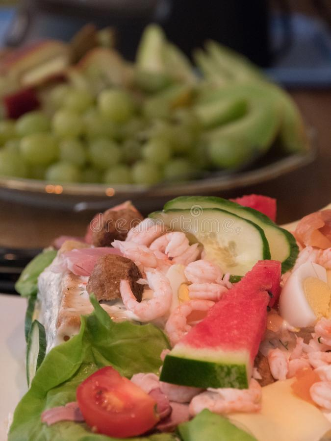 Sandwich layer-cake with shrimps, meatballs and melons stock photo