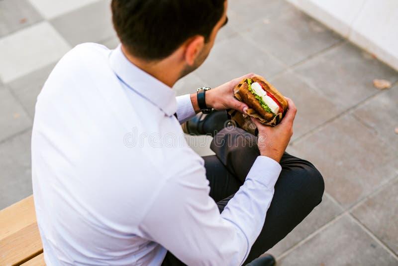 Sandwich mangeur d'hommes à jeunes affaires extérieur image libre de droits