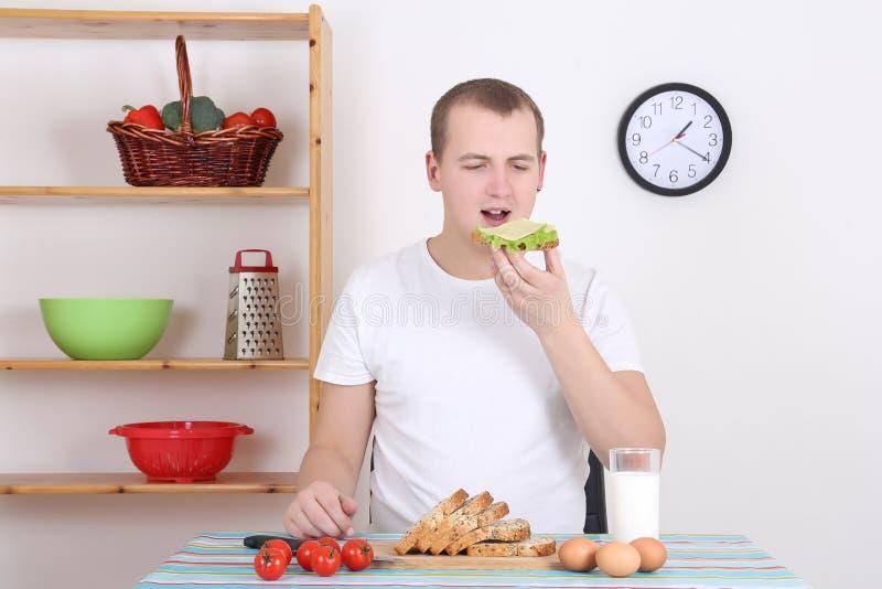 Sandwich mangiatore di uomini con formaggio nella cucina fotografie stock libere da diritti