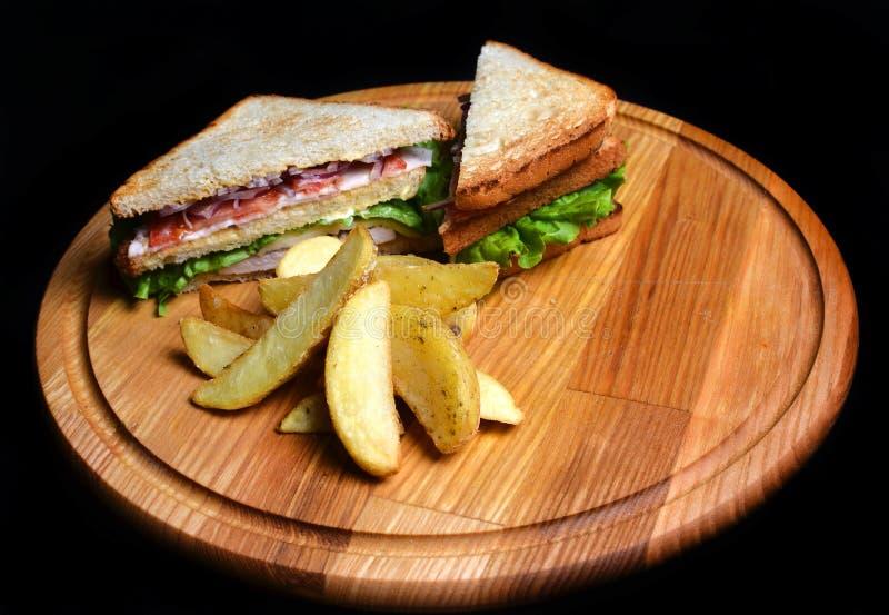 Sandwich met aardappelen in de schil op een houten die raad op witte achtergrond wordt geïsoleerd Restauratedvoedsel Snel voedsel stock fotografie