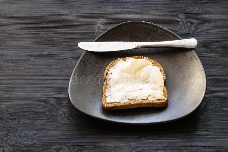Sandwich met beboterde boter en mes op zwarte royalty-vrije stock afbeeldingen