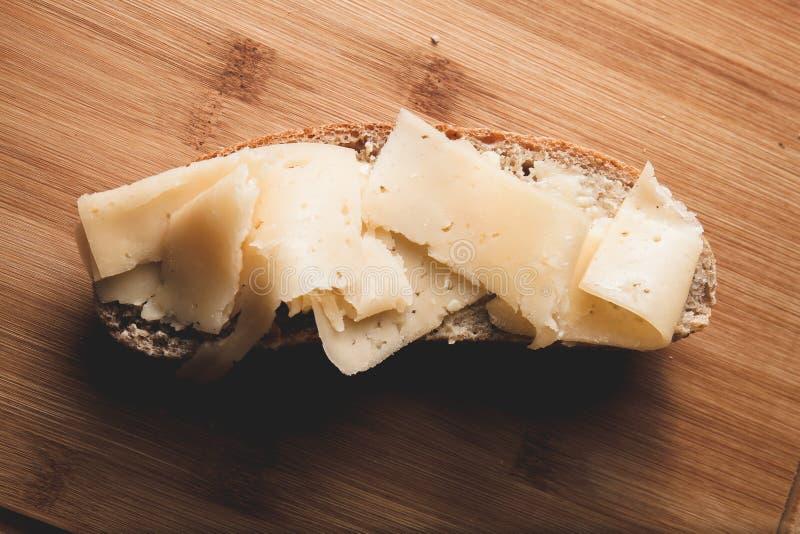 Sandwich met boter en harde kaas op een plak van vers gebakken roggebrood op een houten scherpe raad stock afbeeldingen