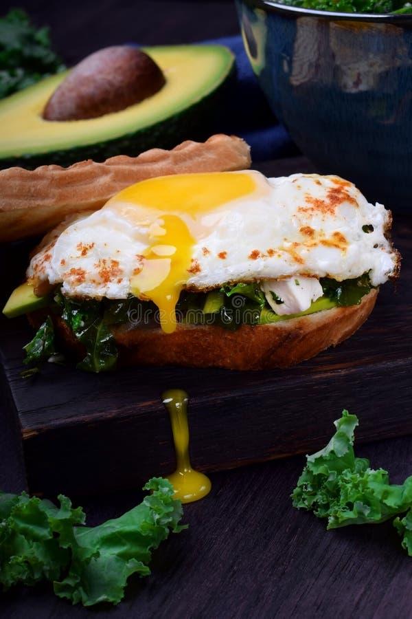 Sandwich met gebraden ei met vloeibare dooier en boerenkoolkool royalty-vrije stock afbeeldingen