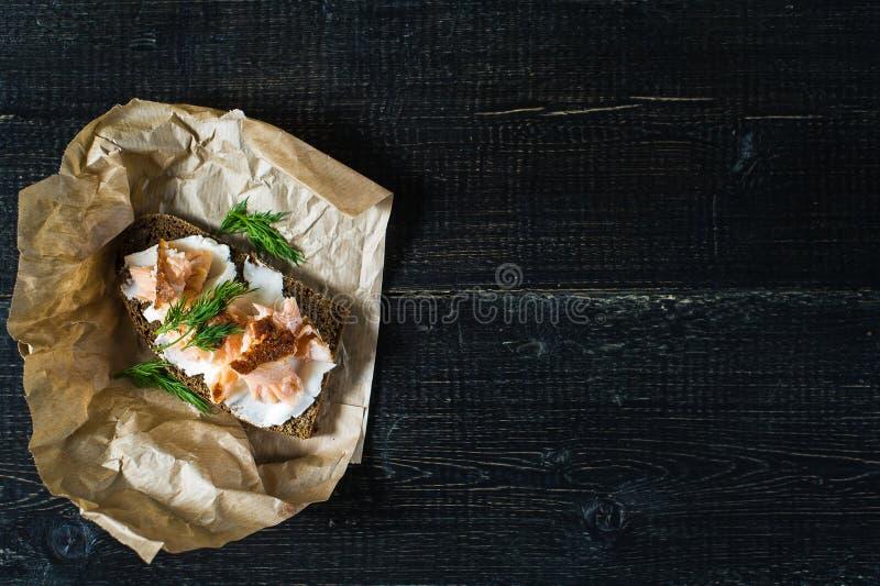 Sandwich met gerookte zalmfilet op zwart brood met zachte kaas stock foto's
