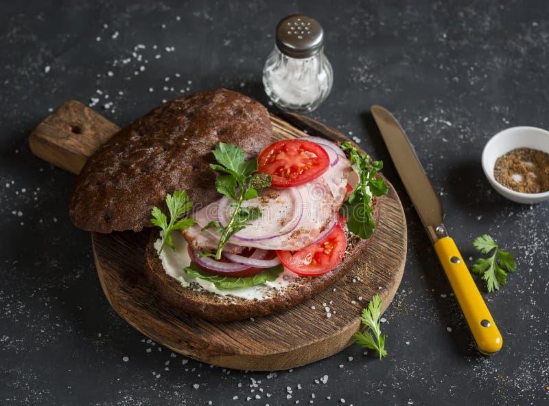 Sandwich met geroosterd varkensvlees, zachte kaas, tomaten en arugula op de houten scherpe raad op donkere achtergrond royalty-vrije stock foto's