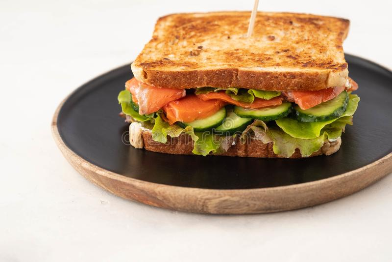 Sandwich met graangewassenbrood en zalm op donkere marmeren achtergrond De ruimte van het exemplaar royalty-vrije stock foto