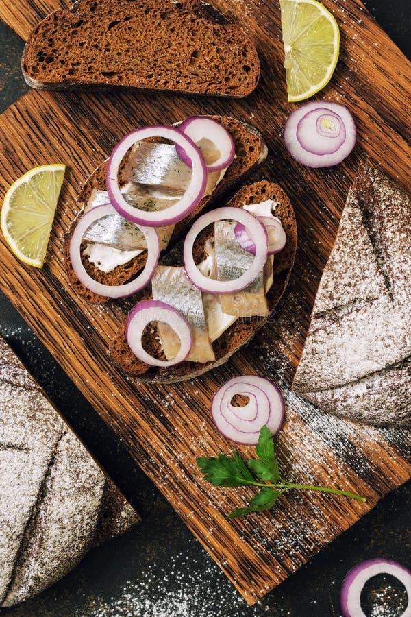 Sandwich met haringen en roggebroodclose-up op een donkere achtergrond Hoogste mening, verticaal kader Deense sandwiches stock afbeelding