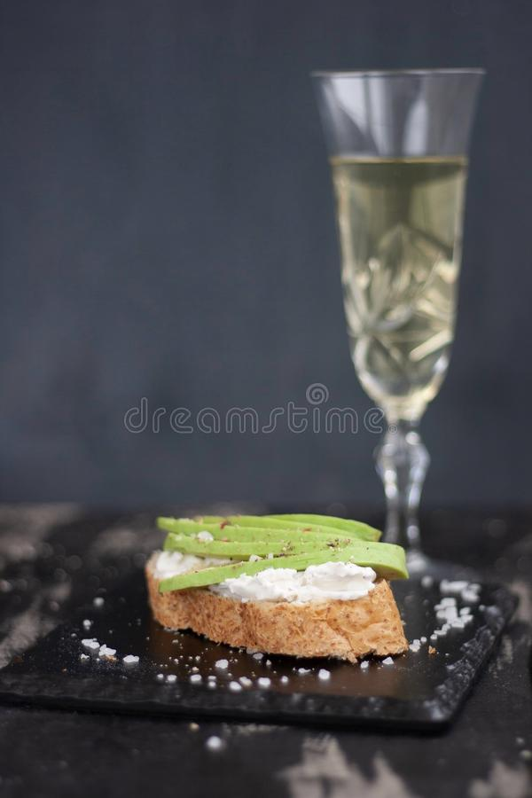 Sandwich met kaas en avocado, glas witte wijn op adarkachtergrond stock afbeelding