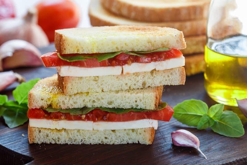 Sandwich met mozarellakaas, tomaten, Basilicum, knoflook en olijfolie stock afbeelding