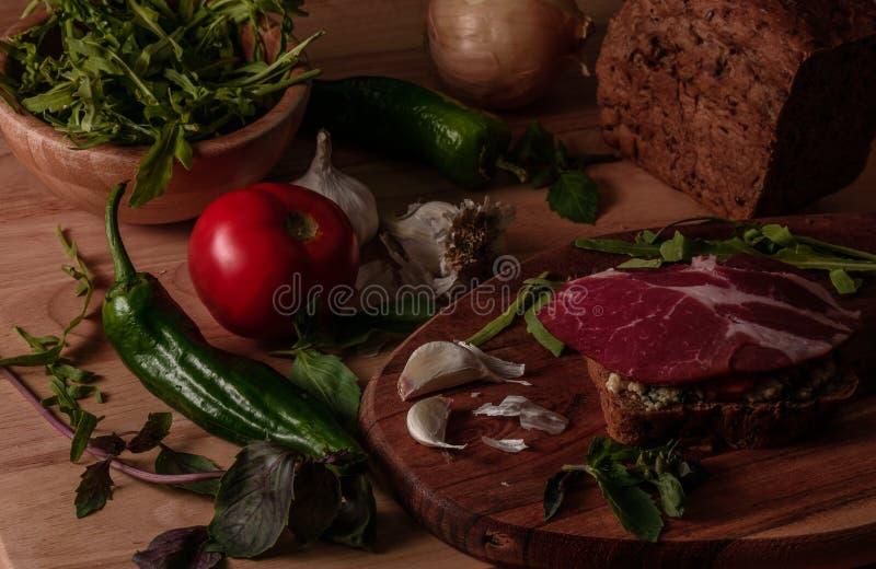 sandwich met pesto, in de zon gedroogde tomaten, basilicum, arugula en gerookt rundvlees stock fotografie