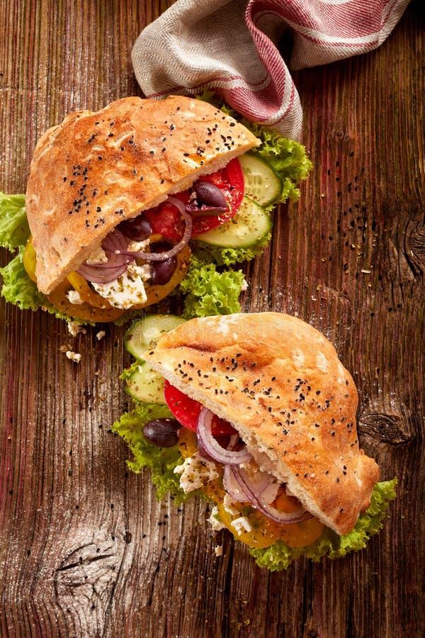 Sandwich met pitabroodje en groenten; tomaat, sla, ui, groene paprika, zwarte olijven een feta-kaas op een houten lijst, bovenkan stock afbeeldingen