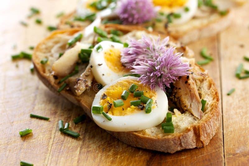 Sandwich mit adition von Makrelenfischen, von Eiern und von essbaren Blumen von Schnittlauchen auf Holztisch lizenzfreie stockbilder