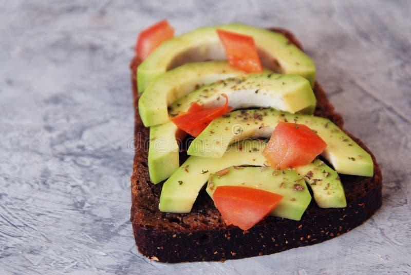 Sandwich mit Avocado und Tomaten - gesundes Frühstückskonzept lizenzfreie stockbilder