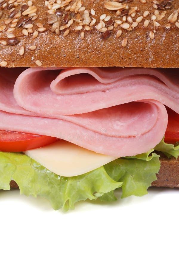 Sandwich mit dem Schinken und Gemüse, den indischen Sesam besprühend lokalisiert stockfotografie